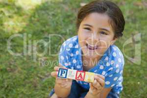 Happy girl holding block alphabets as 'play' at park