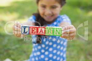 Happy girl holding block alphabets as 'learn' at park