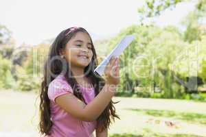Girl playing with a paper plane at park