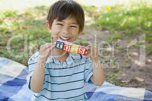 Happy boy holding block alphabets as toys' at park