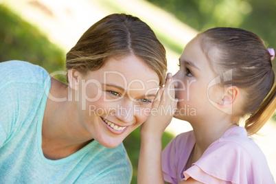 Girl whispering secret into mother's ear at park