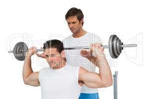 Trainer helping fit man to lift the barbell bench press