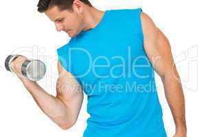Fit young man exercising with dumbbell