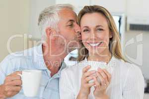 Casual man giving his smiling partner a kiss on the cheek