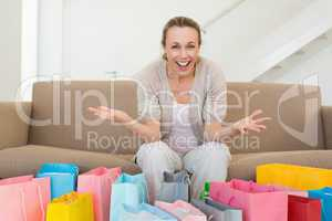 Excited woman looking at camera with many shopping bags