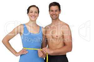 Fit young man measuring womans waist