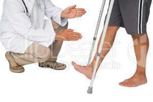 Low section of a doctor with senior man using walker