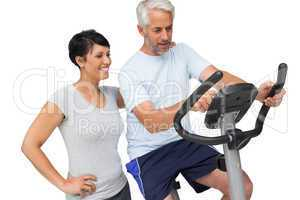 Happy woman looking at mature man on stationary bike