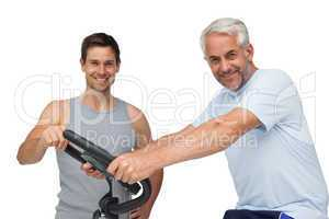 Happy mature man on stationary bike with trainer