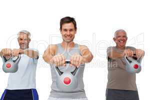 Portrait of three men exercising with kettle bells