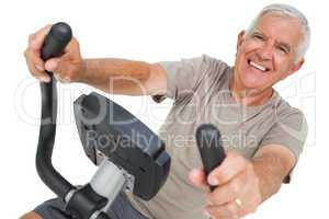 Portrait of a happy senior man on stationary bike