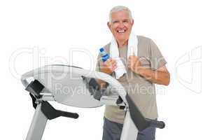 Happy senior man running on a treadmill