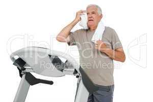 Tired senior man running on a treadmill