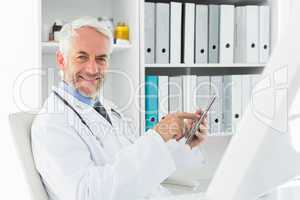 Smiling male doctor using digital tablet at medical office