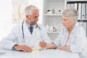 Doctor taking a senior female's pulse