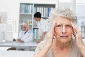 Senior patient suffering from headache with doctors at medical o
