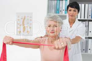 Physiotherapist massaging senior womans back