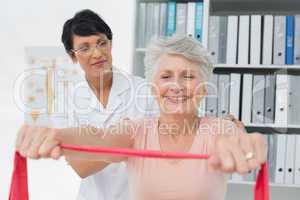 Female physiotherapist massaging senior womans back