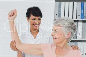 Physiotherapist assisting senior woman to stretch her hand