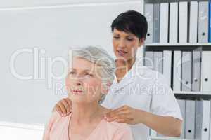 Chiropractor massaging a senior womans shoulder