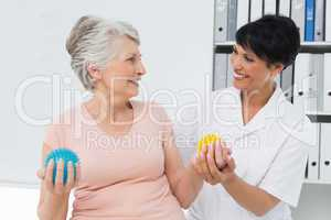 Doctor with senior patient using stress buster balls
