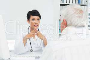 Female doctor attentively listening to senior patient
