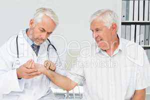 Male doctor taking a senior patients pulse