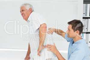 Male physiotherapist examining senior mans back