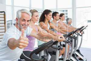 Man gesturing thumbs up with class at spinning class