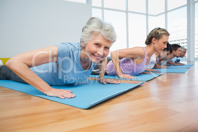 Group doing cobra pose in row at yoga class