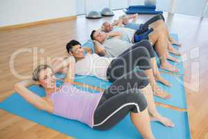 Class lying on mats in row at yoga class