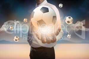 Businessman presenting floating footballs