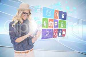 Stylish blonde using tablet pc with app icon menu