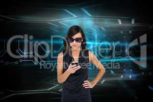 Glamorous brunette using smartphone against circuit board