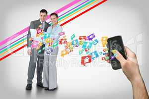 Hand holding smartphone with app icons and business partners beh