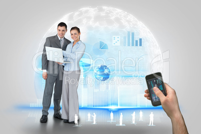 Hand holding smartphone with interface and business partners beh