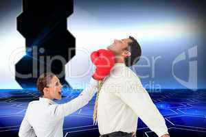 Composite image of businesswoman hitting a businessman with boxi
