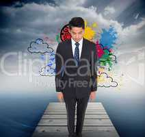 Composite image of serious businessman looking down