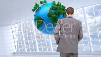 Composite image of young businessman walking away from camera