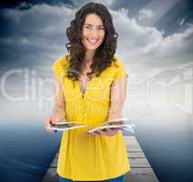 Composite image of cheerful curly haired brunette reading magazi