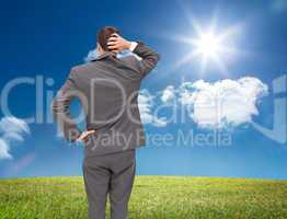 Composite image of young businessman standing back to camera scr