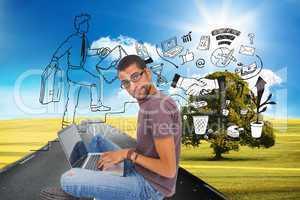 Composite image of man wearing glasses sitting on floor using la
