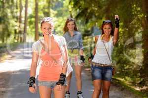 three women friends roller skating outdoors