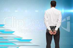 Composite image of rear view of young businessman wearing handcu