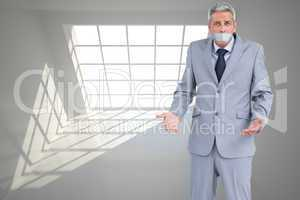 Composite image of businessman gagged with adhesive tape on mout