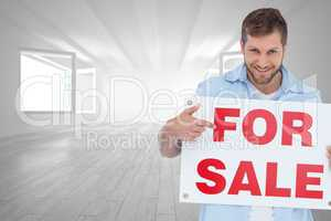 Composite image of smiling model holding a for sale sign