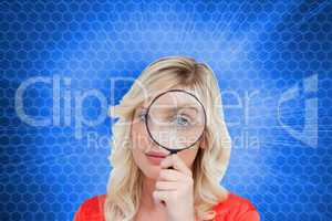 Composite image of fair-haired woman looking through a magnifyin