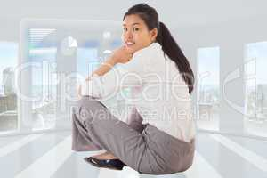 Composite image of businesswoman sitting cross legged smiling