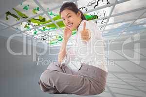 Composite image of businesswoman sitting cross legged showing th