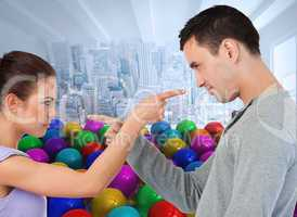Composite image of young couple pointing at each other